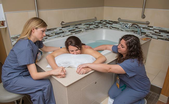 Woman in a tub giving birth with two nurses holding her hands