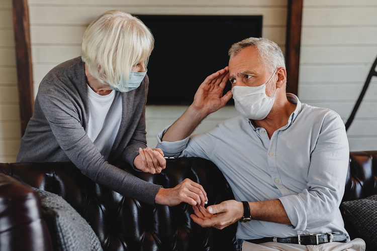 A woman hands a man a small white pill, while the man with a headache rubs his temple. Both are wearing paper face masks in their home.