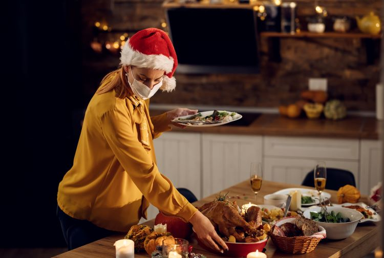 Woman wearing Santa hat and face mask selecting food from table