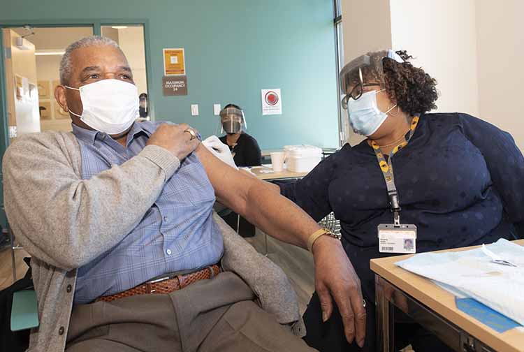 Kimberly Battle vaccinates her father, Phillip Battle