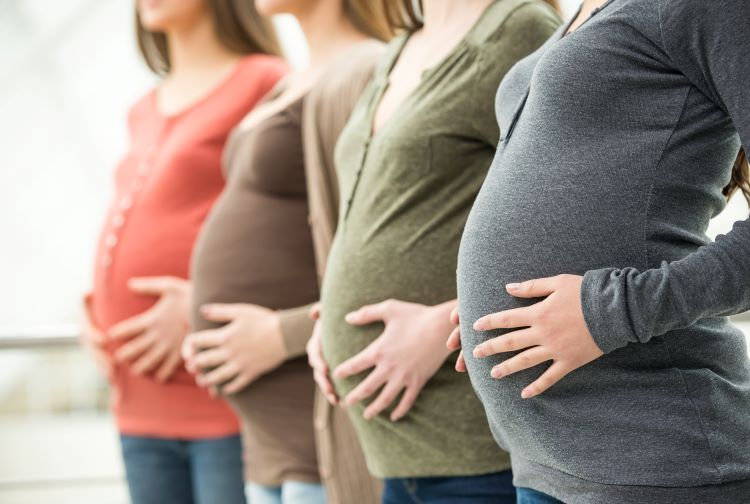 Four pregnant women standing together
