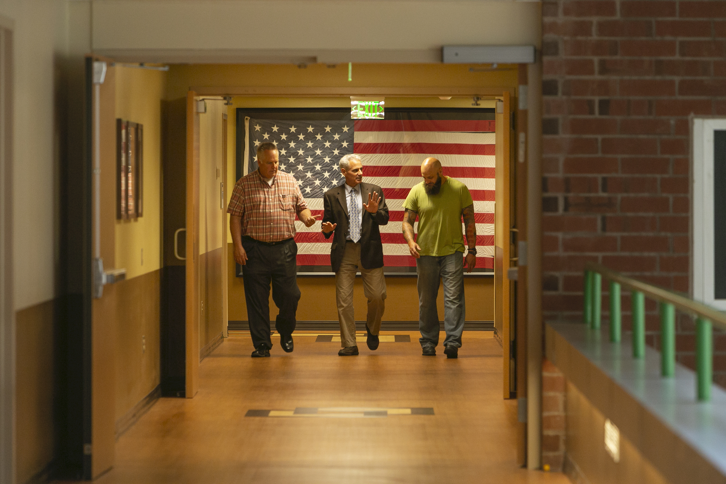 Three people walk down the corridor of a hospital. The flag of the United States is displayed behind them.