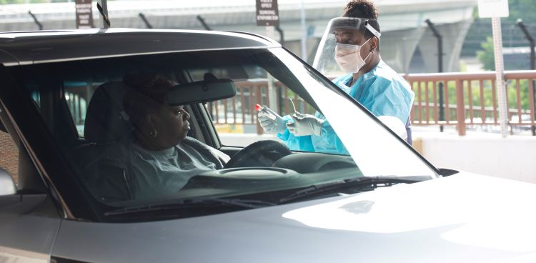 Medical provider in PPE standing next to a car with a driver.