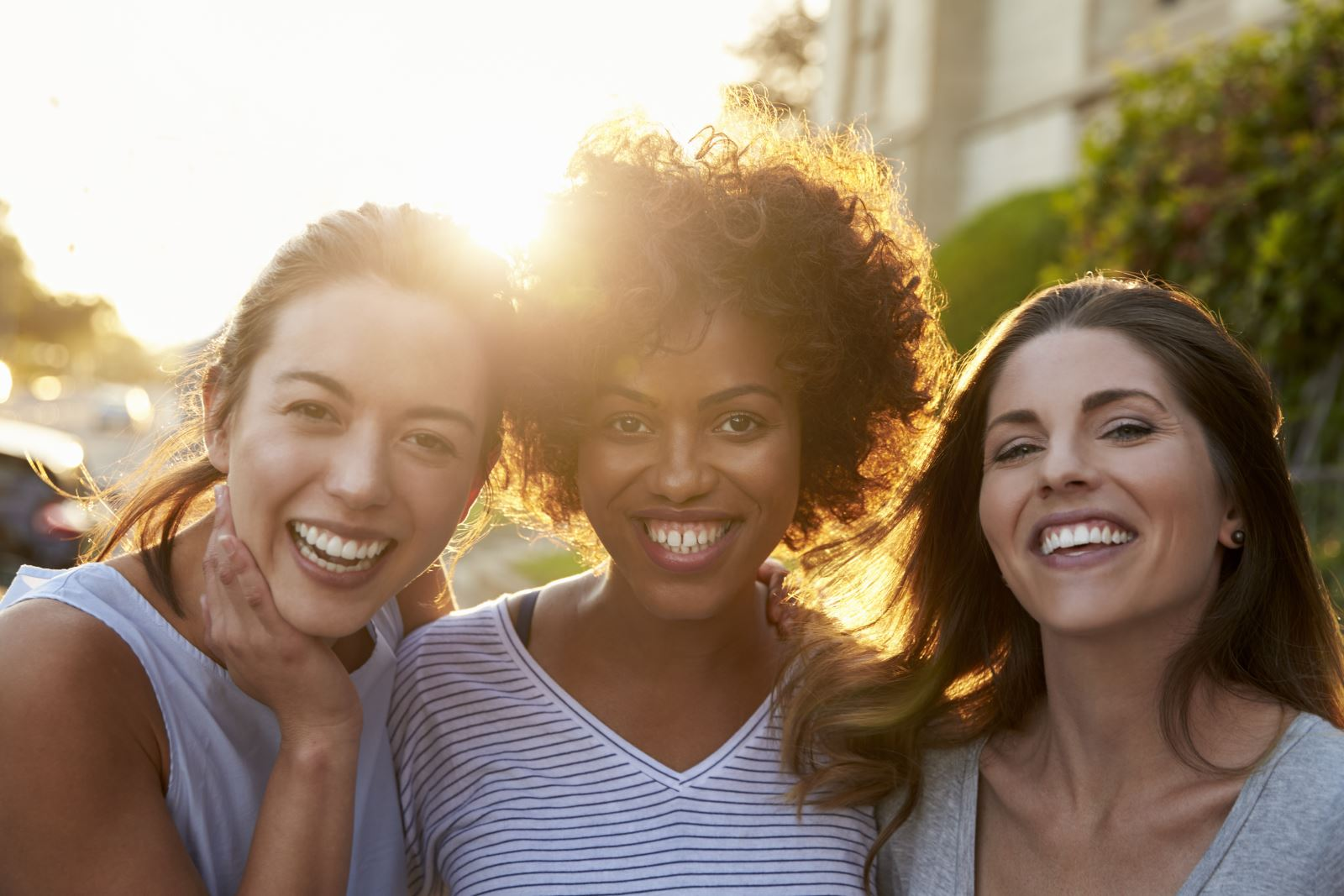 Three smiling women of different ages and ethnicities looking into the camera with the sun behind them.