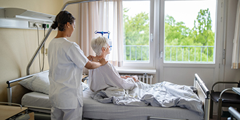 Woman sitting on a hospital bed looking out the window. She is having her neck massaged by a healthcare provider.