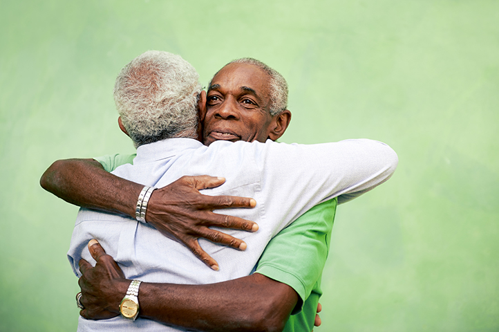 Two men hugging and smiling